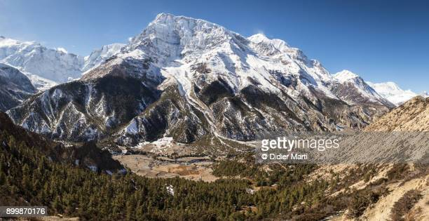 panorama of the annapurna iii summit near the town of manang along the annapurna circuit trek in the himalayas in nepal - annapurna circuit stock photos and pictures