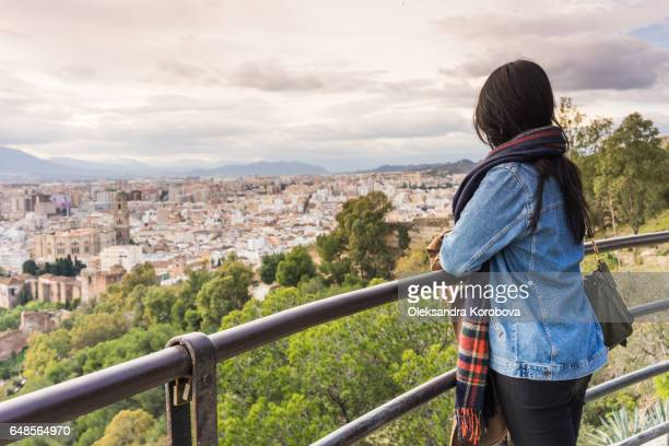 malaga, spain - december 19, 2016. panorama of the city of malaga, spain from the walls and towers of an ancient medieval castle of gibralfaro. young woman looking over the town on a sunny day with her back to the camera. view from behind. - istock photos et images de collection