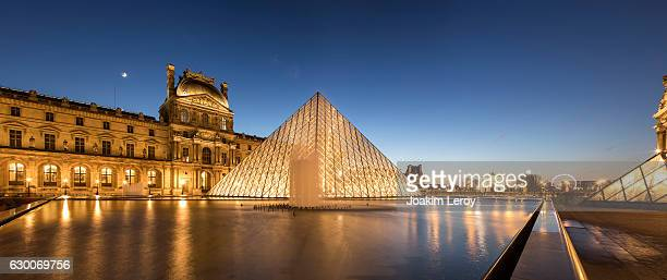 panorama of the iconic louvre museum in paris at sunset - louvre photos et images de collection