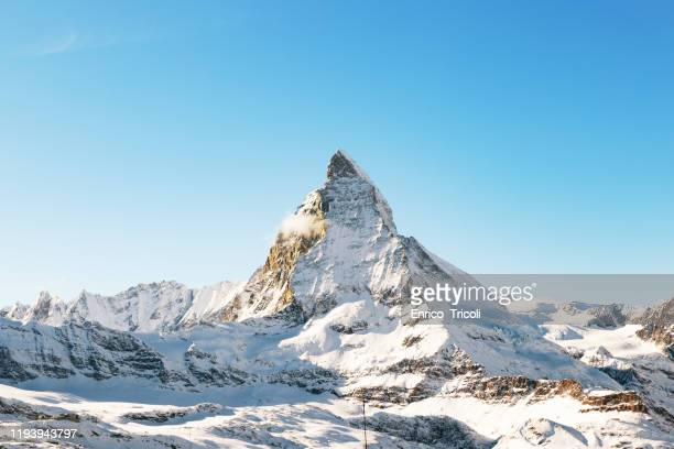 panorama of the matterhorn mountain range, covered with fresh snow, and blue sky in the cloudless background. christmas season, winter and ski slopes on the swiss alps. - matterhorn stock pictures, royalty-free photos & images