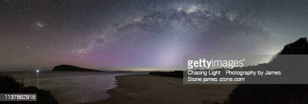panorama of the milky way with a beam of zodiacal light underneath and a subtle aurora. - aurora australis stock pictures, royalty-free photos & images