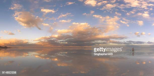 panorama of two photographers taking photograph with reflection in the lake, water flooded salt lake, Salar de Uyuni, Altiplano, Bolivia