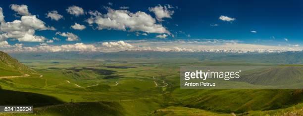 panorama of view from pass to green valley and the mountains. kyrgyzstan - flanco de valle fotografías e imágenes de stock