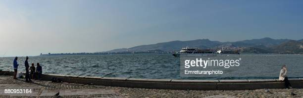 panorama of waterfront with fishermen,woman on the phone and ferries travelling across the bay in izmir. - emreturanphoto stock pictures, royalty-free photos & images