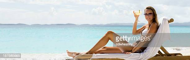 panorama of woman relaxing at the beach drinking margarita cocktail - margarita beach stock photos and pictures