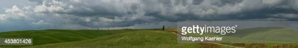 Panorama photo of storm clouds over a field with red flowers and a road near San Quirico in the Val d'Orcia near Pienza in Tuscany, Italy.