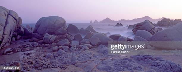 Panorama view at dusk of boulders and rock formations along the coastline with the Arch of Cabo San Lucas at Lands End in the background.