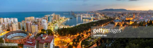 panorama view of port and centre of malaga city at dusk, andalucía, spain - málaga málaga province stock pictures, royalty-free photos & images