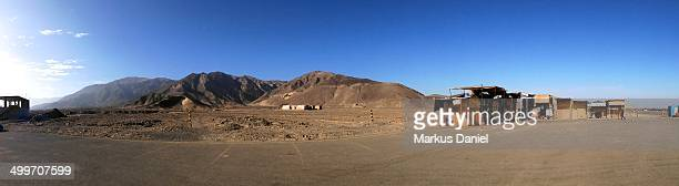 CONTENT] Panorama view of the Airport in Naza Peru with view to the back parking lot desert mountains souvenir shops and the runway to the very right