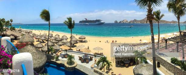 A panorama view of the beach and  cruise ship with  palapas in the foreground at  Playa El Medano, Cabo San Lucas.
