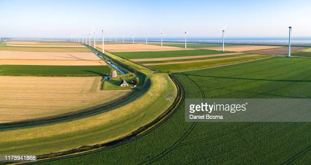 panoramic aerial of a old historical windmill in a polder surrounded by modern wind turbines - groningen stockfoto's en -beelden