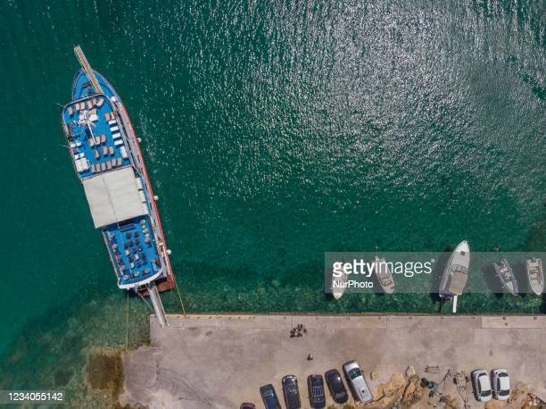 Panoramic aerial view from a drone of Agios Giorgios or Katigiorgis Village, beach and harbor in Pelion region in Greece with sunshine during summer...
