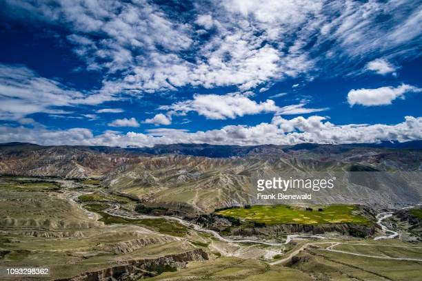 Panoramic aerial view on buckwheat and barley fields and the barren landscape of Upper Mustang, dark monsoon clouds approaching.