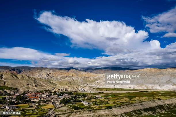 Panoramic aerial view on the town, the agricultural surroundings and the barren landscape of Upper Mustang, dark monsoon clouds approaching.