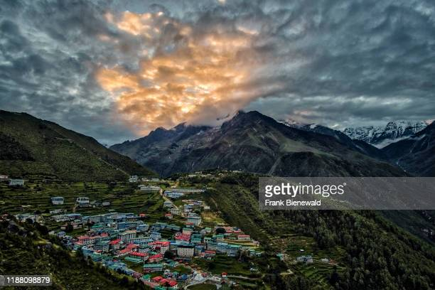 Panoramic aerial view over the town at sunrise, mountainous landscape covered in monsoon clouds in the distance.