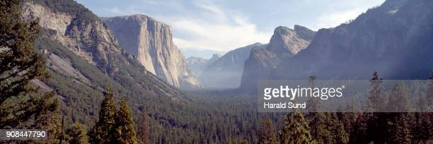 Panoramic afternoon view from Wawona Tunnel showing the forest covered glacial carved valley of Yosemite National Park with Half Dome and El Capitan.