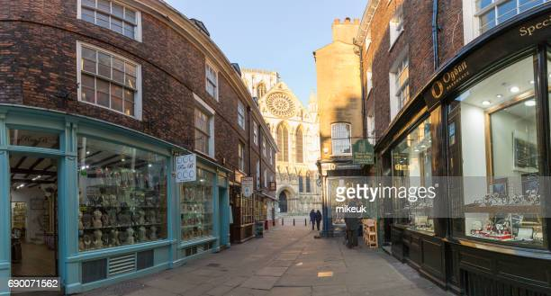 panoramic architectural view of a shopping street in the city centre of york with the famous minster cathedral in the background - york yorkshire stock photos and pictures