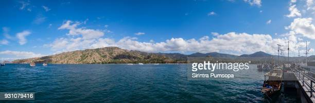 Panoramic blue sky background with white clouds on a sunny day over the sea with the Concrete pier to Komodo National Park in Komodo island.