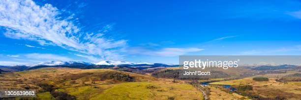 panoramic drone view of snow on distant hills - johnfscott stock pictures, royalty-free photos & images