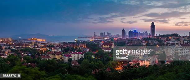 panoramic dusk view of qingdao city,panorama city - miragec stock pictures, royalty-free photos & images