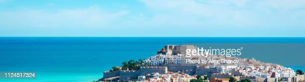 panoramic image horizontal view from distance castillo del papa luna castle, spanish charming picturesque place, sunny day, bright color - altea stock photos and pictures