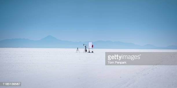 a panoramic image of a small movie set with tripod,  camera, and diffuser in the middle of white bonneville raceway salt flat with blue sky in the background. wendover, utah, usa - film set stock pictures, royalty-free photos & images