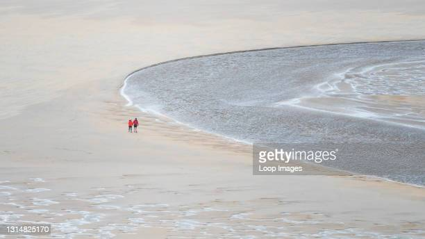 Panoramic image of walkers seen from a distance walking at low tide across Crantock Beach in Newquay in Cornwall.