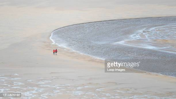 Panoramic image of walkers seen from a distance walking at low tide across Crantock Beach as the River Gannel flows to the sea in Newquay in Cornwall.