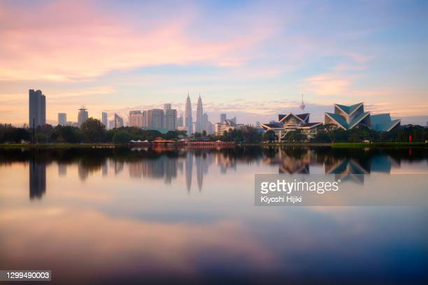 panoramic kuala lumpur cityscape reflects on lake from titiwangsa park in malaysia - malaysia stock pictures, royalty-free photos & images