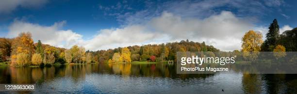 Panoramic landscape of the lake and autumnal trees at the Stourhead estate in Wiltshire England on November 4 2019