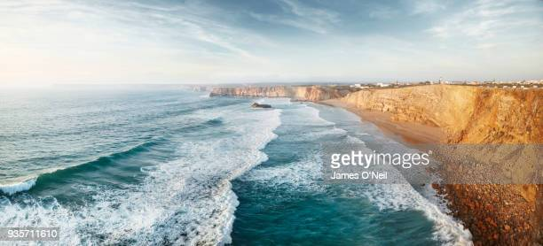 panoramic looking down at sagres beach and waves in the ocean, algarve, portugal - algarve stock photos and pictures
