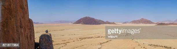 Panorama von einem Mann mit dem Fernglas hoch oben auf einem einsamen Felsen