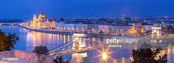 panoramic of chain bridge and parliament in budapest at dusk - budapest stock pictures, royalty-free photos & images