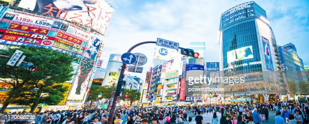 panoramic of people walking across shibuya crossing in downtown tokyo, japan - powerofforever stock pictures, royalty-free photos & images