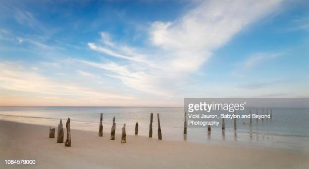 panoramic of posts, calm water and clouds at fort myers beach, florida - fort myers beach stock pictures, royalty-free photos & images