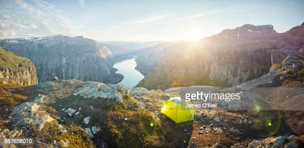 Panoramic of tent overlooking mountainous terrain at sunset, Norway