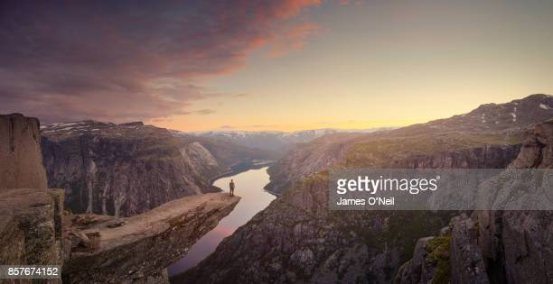 Panoramic of traveller looking out at landscape at sunset, Trolltunga, Norway