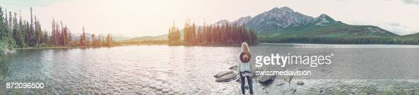 Panoramic of young woman looking at mountains from lakeshore, Canada