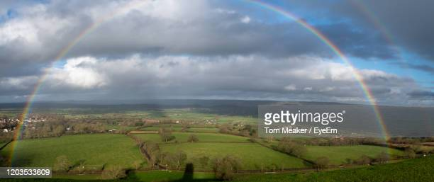 panoramic photo of a rainbow in the countryside - glastonbury england stock pictures, royalty-free photos & images