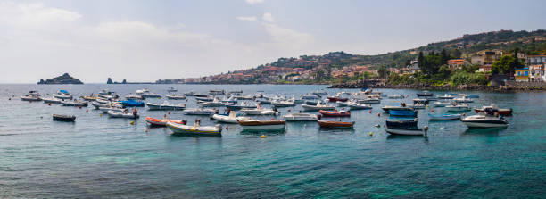Panoramic photo of boats in the harbor at Aci Trezza with Isole dei Ciclope in the background, just outside Catania, Sicily, Italy, Europe