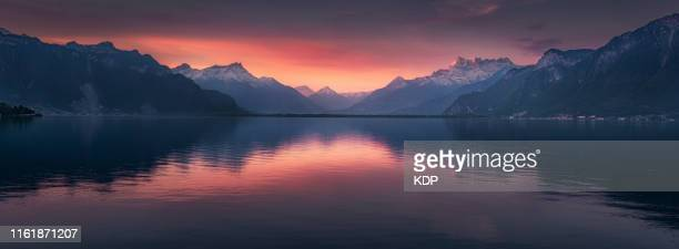 panoramic scenery of lake geneva with mountains range at sunrise in vevey, switzerland - kanton waadt stock-fotos und bilder