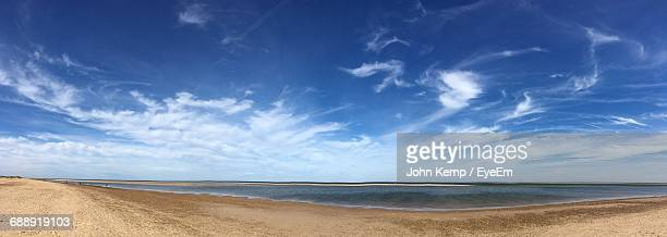 panoramic shot of beach against sky - panoramic stock pictures, royalty-free photos & images