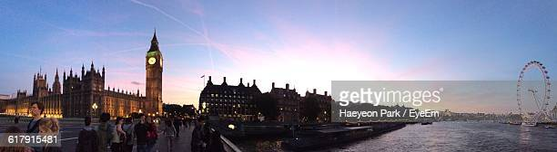 Panoramic Shot Of Big Ben With Thames River And Millennium Wheel Against Sky During Sunset