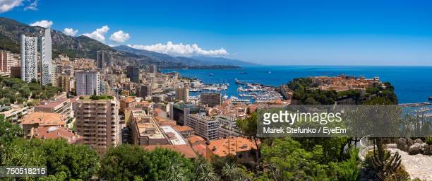 panoramic shot of city by sea against blue sky - marek stefunko stock photos and pictures
