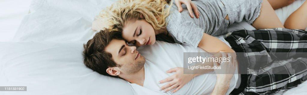 Panoramablicke von glücklichen Paaren, die sich umarmten, während sie auf dem Bett liegen : Stock-Foto