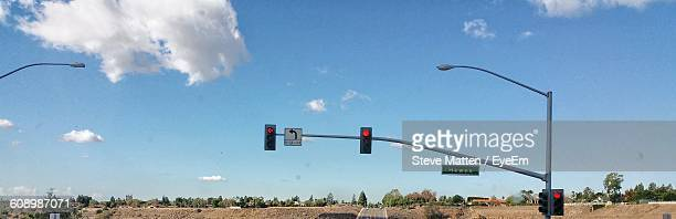 panoramic shot of road signal over field against sky - steve matten stock pictures, royalty-free photos & images