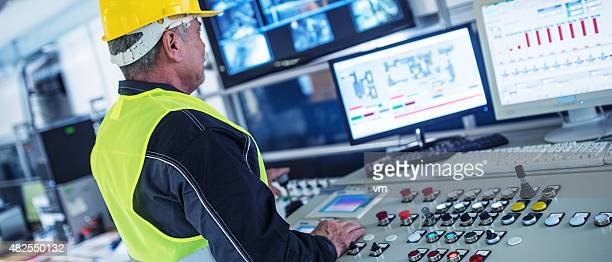 panoramic shot of technician in control room - automated stock pictures, royalty-free photos & images