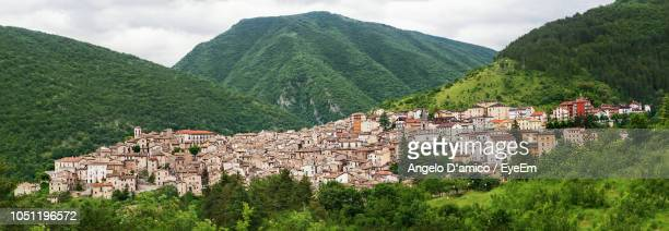 Panoramic Shot Of Townscape By Mountain Against Sky