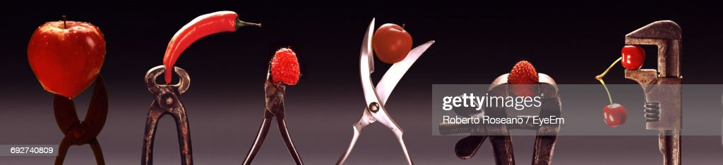 Panoramic Shot Of Work Tools With Red Fruits And Vegetables Against Colored Background : Stock Photo