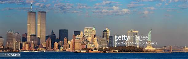 Panoramic sunset view of World Trade Towers Statue of Liberty Brooklyn Bridge and Manhattan NY skyline
